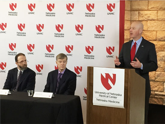 Governor Pete Ricketts speaks during a press event for the 10th anniversary of the University of Nebraska Medical Center Biocontainment Unit. Dr. Rick Sacra (left) and Dr. Phil Smith (right) are seated.